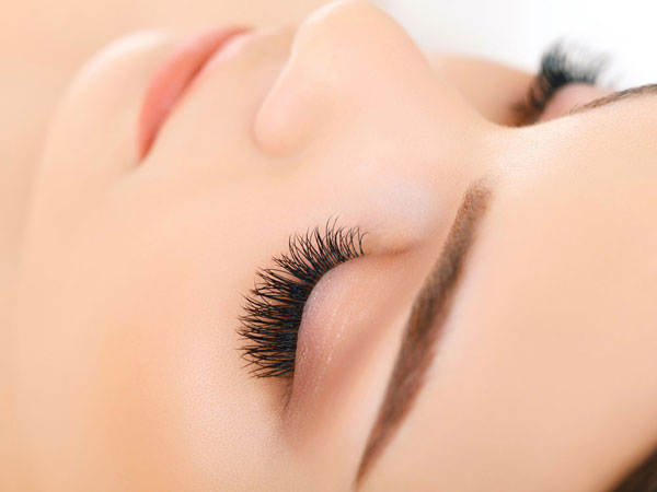 closeup of long eyelashes and filled in brows with smooth skin