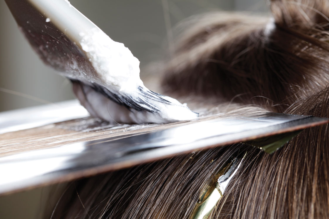 color being applied to a section of hair on a foil with a brush