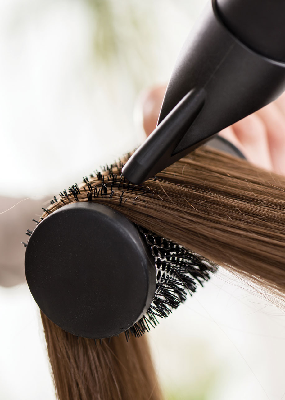 brown hair on a round brush being blown dry